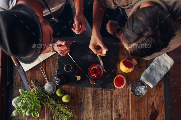 Two bartenders discussing creative recipe ideas for cocktails - Stock Photo - Images
