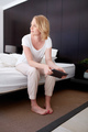 Mature woman with a digital tablet on bed
