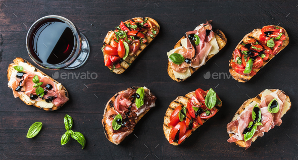 Brushetta snacks for wine. Variety of small sandwiches on dark rustic wooden backdrop - Stock Photo - Images