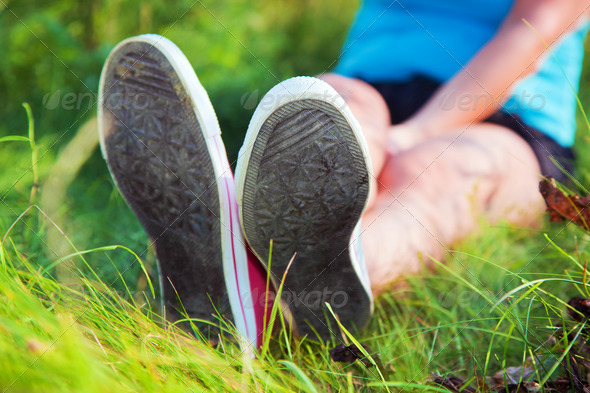 Pink sneakers on girl legs on grass - Stock Photo - Images