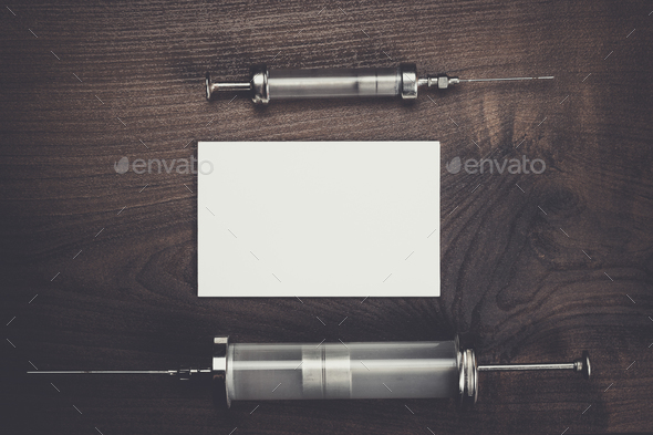 retro medical syringes and notebook over wooden background - Stock Photo - Images