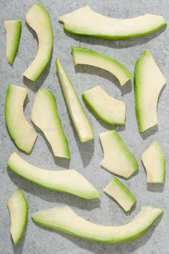 Avocado slices on stone background