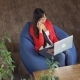 Asian Woman Working In Loft Sitting On Bean Bag Chairs - VideoHive Item for Sale