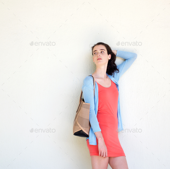 Stylish Young Woman Carrying A Purse Leaning Against Wall