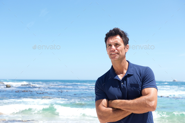 Rugged middle aged man standing at the beach - Stock Photo - Images