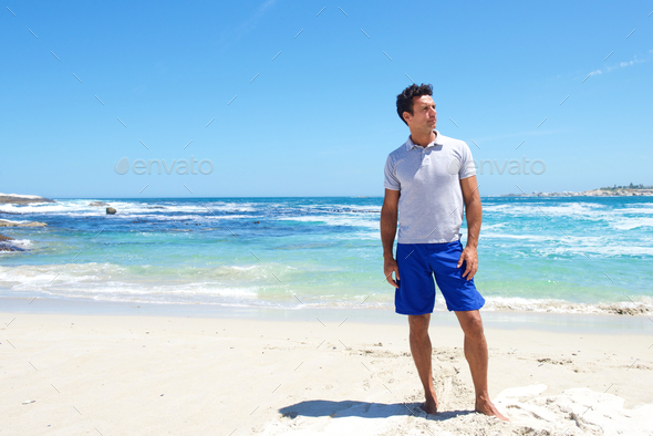 Fit middle aged man standing barefoot at the beach - Stock Photo - Images