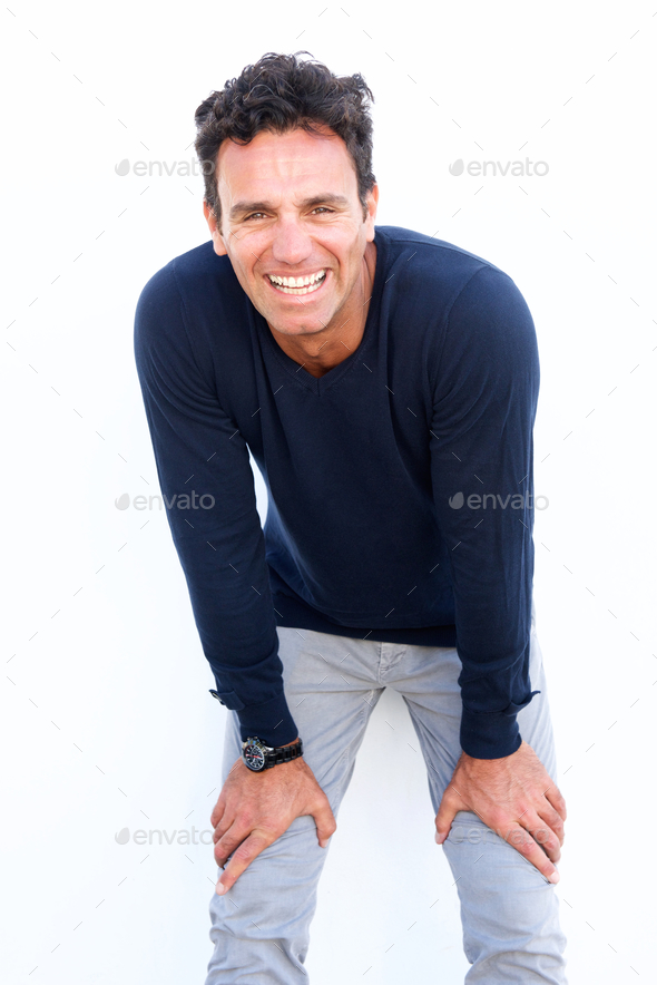 Handsome middle aged man laughing with hands on knees - Stock Photo - Images