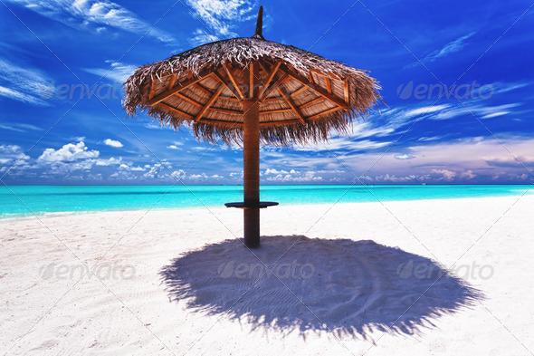 Beach umbrella on white sand next to lagoon - Stock Photo - Images