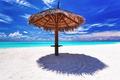 Beach umbrella on white sand next to lagoon - PhotoDune Item for Sale