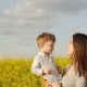 Mother Holding Her Son At Field At Sunset.  - VideoHive Item for Sale