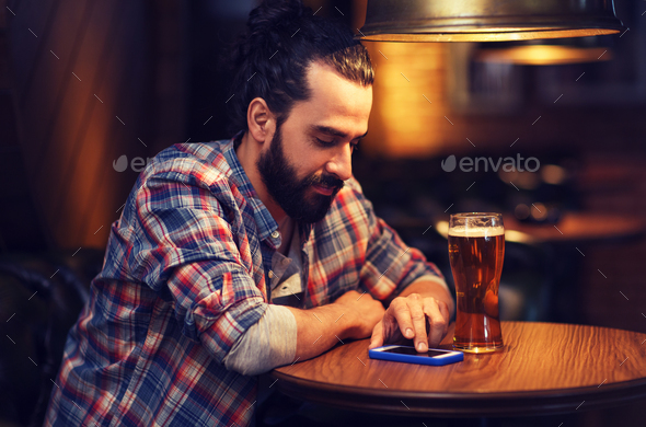 man with smartphone and beer texting at bar - Stock Photo - Images