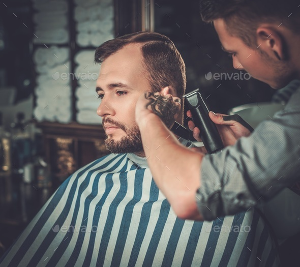 Confident man visiting hairstylist in barber shop. - Stock Photo - Images