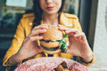 Close up on the hands of a young woman sitting holding an hamburger - PhotoDune Item for Sale