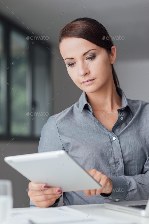 Confident businesswoman using a digital tablet - Stock Photo - Images