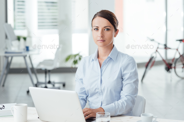Young businesswoman at office desk - Stock Photo - Images