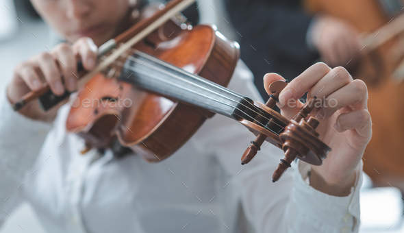 Violinist tuning a violin - Stock Photo - Images