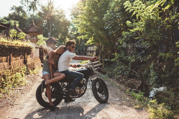 Young man and woman on motorbike in a village - Stock Photo - Images