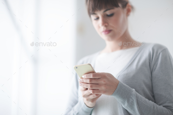 Young woman text messaging with her mobile - Stock Photo - Images