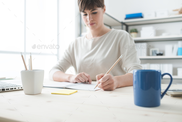Young woman sketching on a notebook - Stock Photo - Images