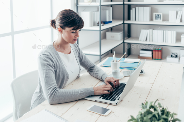 Confident businesswoman working at desk - Stock Photo - Images