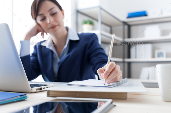 Businesswoman writing notes on a notebook - Stock Photo - Images