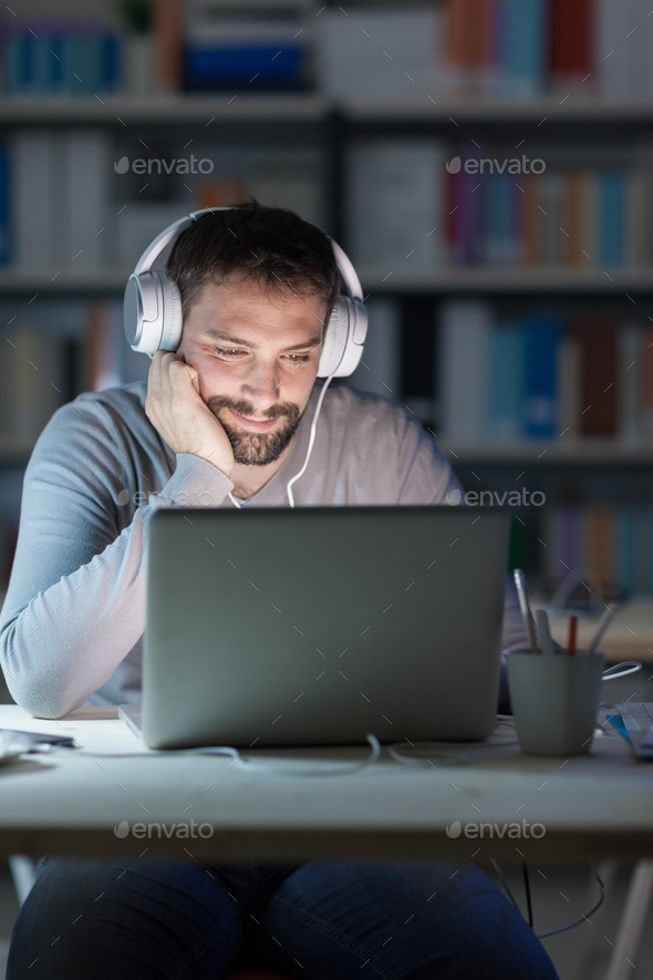 Smiling man networking late at night - Stock Photo - Images