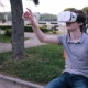 Young Handsome Man Wearing Virtual Reality Goggles Sitting In a City Park. - VideoHive Item for Sale