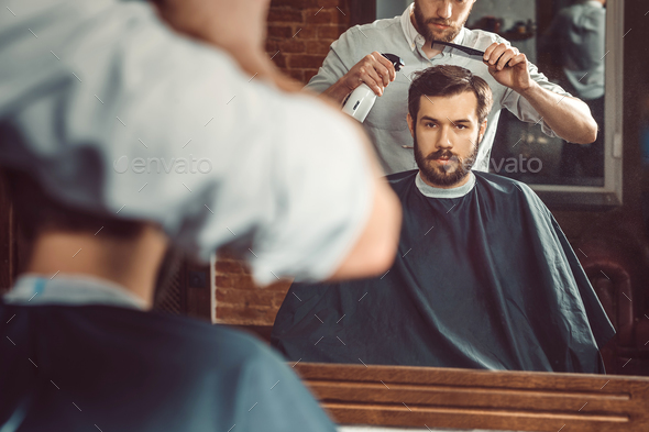 Young handsome barber making haircut of attractive man in barbershop - Stock Photo - Images