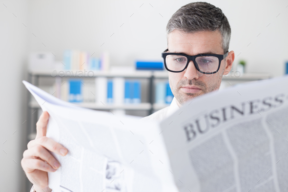Confident businessman reading a newspaper - Stock Photo - Images