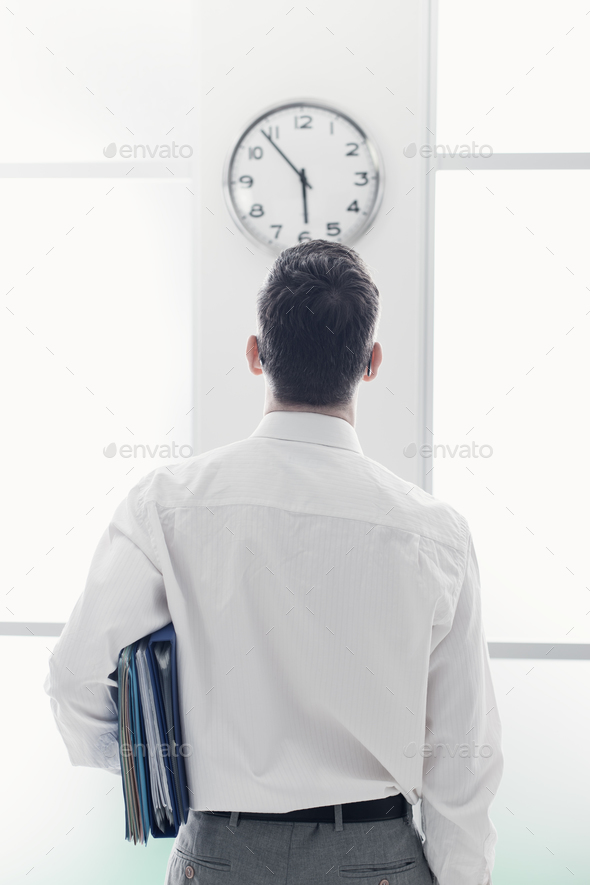 Businessman staring at the clock - Stock Photo - Images