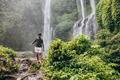 Young man walking along mountain trail