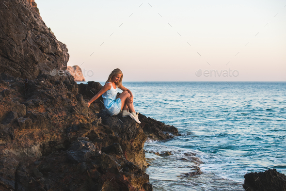 Young blond woman tourist in blue dress sitting - Stock Photo - Images