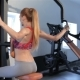 Woman Sits Backwards On The Bench Of Gym Machine At The Fitness Centre - VideoHive Item for Sale