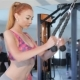 Woman Trains Her Back And Arm Muscles On Gym Machine At The Fitness Centre - VideoHive Item for Sale