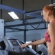 Woman Puts Earphones In Her Ears On Treadmill At The Fitness Centre - VideoHive Item for Sale