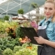 Female Florist Holds Black Tablet At The Garden Centre - VideoHive Item for Sale