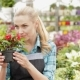 Female Florist Smells Red And White Flowers At The Garden Centre - VideoHive Item for Sale