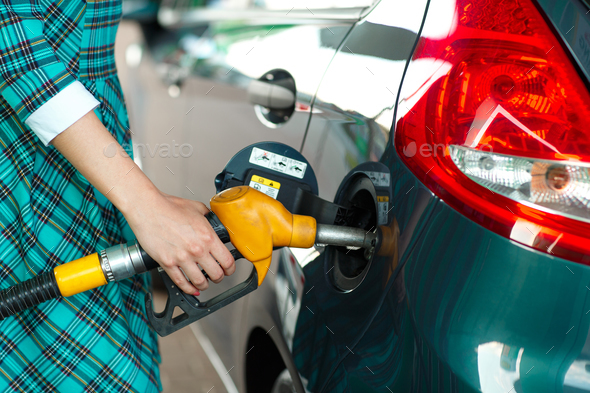 Woman fills petrol into her car at a gas station - Stock Photo - Images