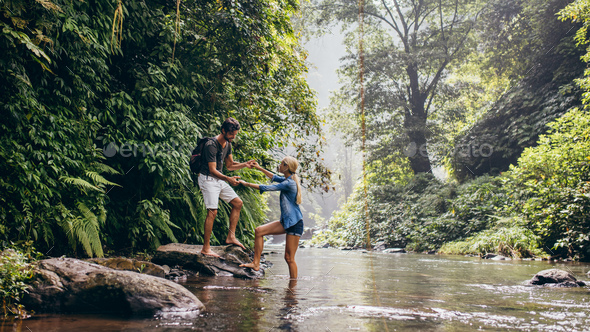 Man helping woman crossing stream - Stock Photo - Images