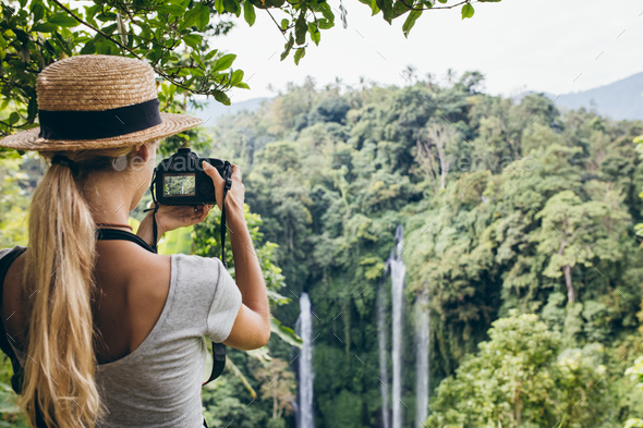 Female tourist photographing a waterfall in forest - Stock Photo - Images