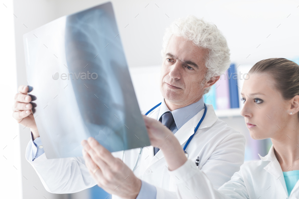 Radiologist checking an x-ray with his assistant - Stock Photo - Images