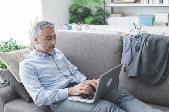 Businessman working from the couch - Stock Photo - Images