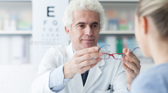 Optician giving glasses to the patient - Stock Photo - Images