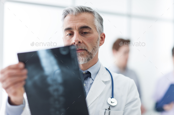 Radiologist examining a patient's x-ray - Stock Photo - Images