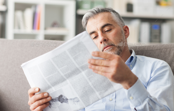 Businessman reading a newspaper - Stock Photo - Images
