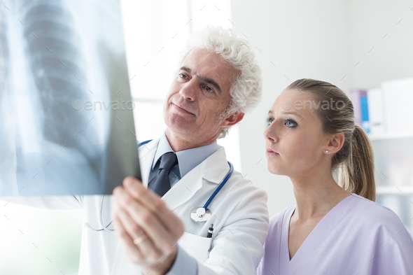 Doctors examining an x-ray image - Stock Photo - Images