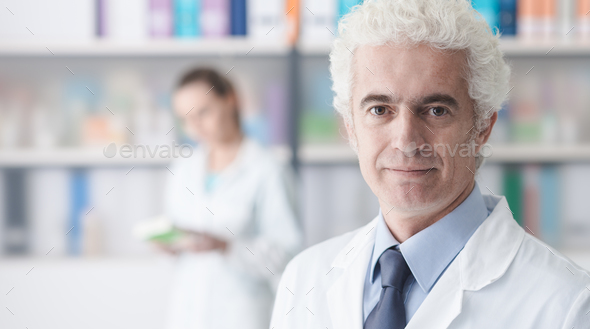 Confident doctor posing in his office - Stock Photo - Images
