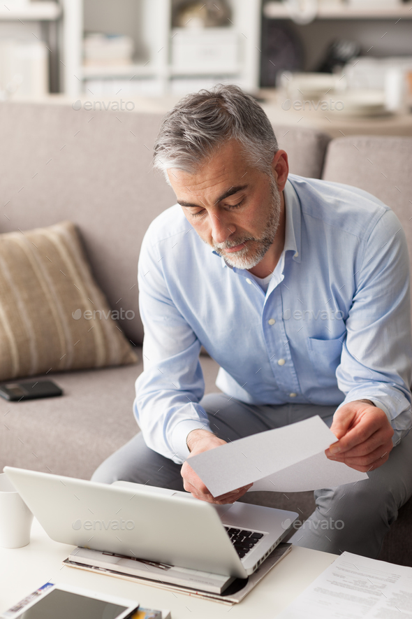 Businessman checking bills - Stock Photo - Images