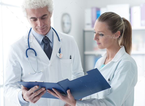 Doctor checking medical records - Stock Photo - Images