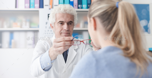 Ophthalmologist giving glasses to the patient - Stock Photo - Images
